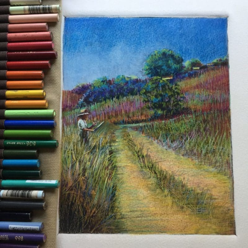 A dark field monotype of a grassy meadow with hills in the background and an artist working on her easel in the tall grasses, with a row of colored pencils next to the print