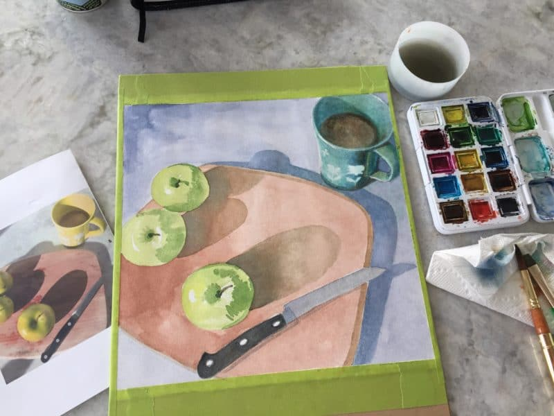 the beginnings of a still life watercolor painting with the reference material on one side and the painting palette on the other