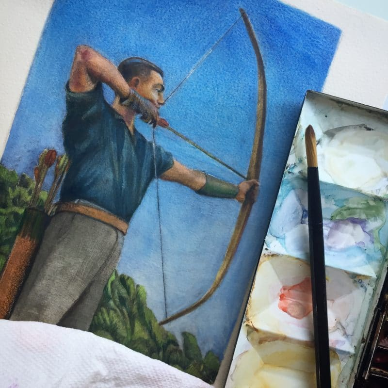 a watercolor palette next to an in process drypoint of an archer
