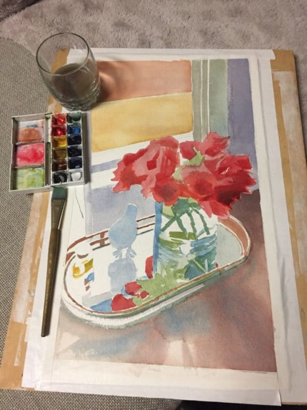 A watercolor painting of a still life being painted in glazes shown in the early stages of laying in shapes and base colors