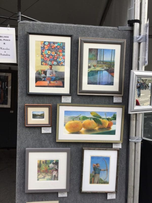 an art exhibit display panel at a festival outdoors with a group of paintings framed on display