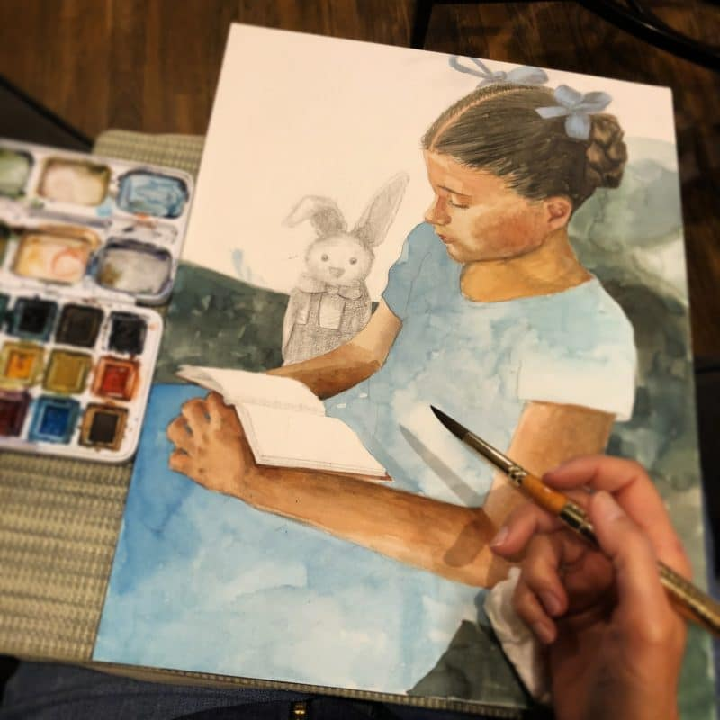 A lap desk on the couch with a watercolor of a little girl reading in process next to a small watercolor palette