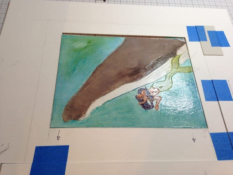 an inked collagraph plate of a mermaid and a whale, about to be printed on an etching press