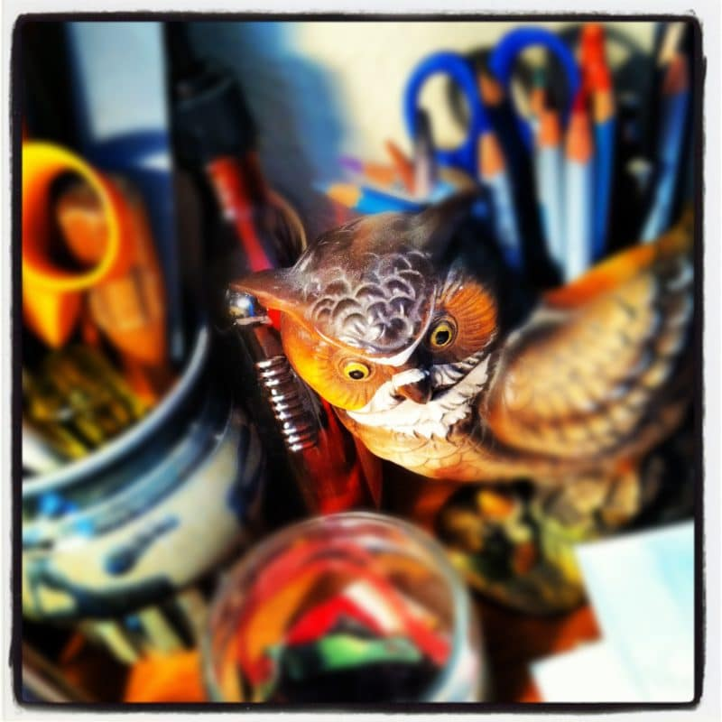a cermaic vase in the shape of an owl filled with colored pencils, paint brushes, and art supplies