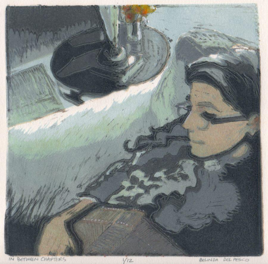 Multi-color linocut in soft colors of a woman sitting in an overstuffed chair with a book in her lap