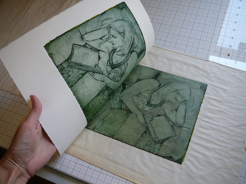 after a trip through the etching press, a collagraph print of a woman reading in bed against pillows is pulled from the plate in green ink