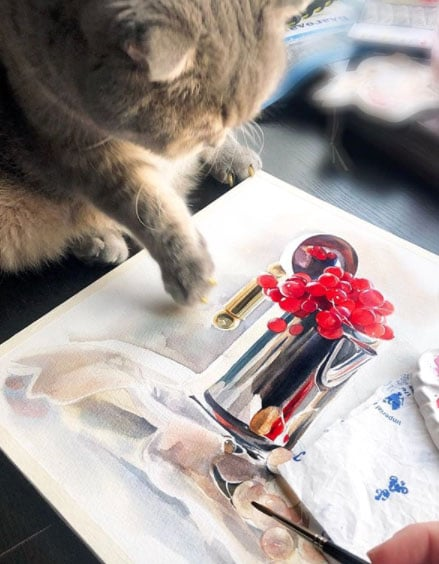 A watercolor still life in process with a cat coming into the frame