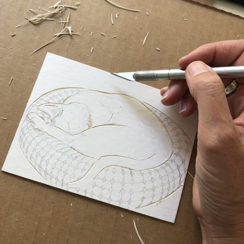 a hand holding an exacto knife, and cutting fine lines and pattern details out of the surface of a sheet of matboard