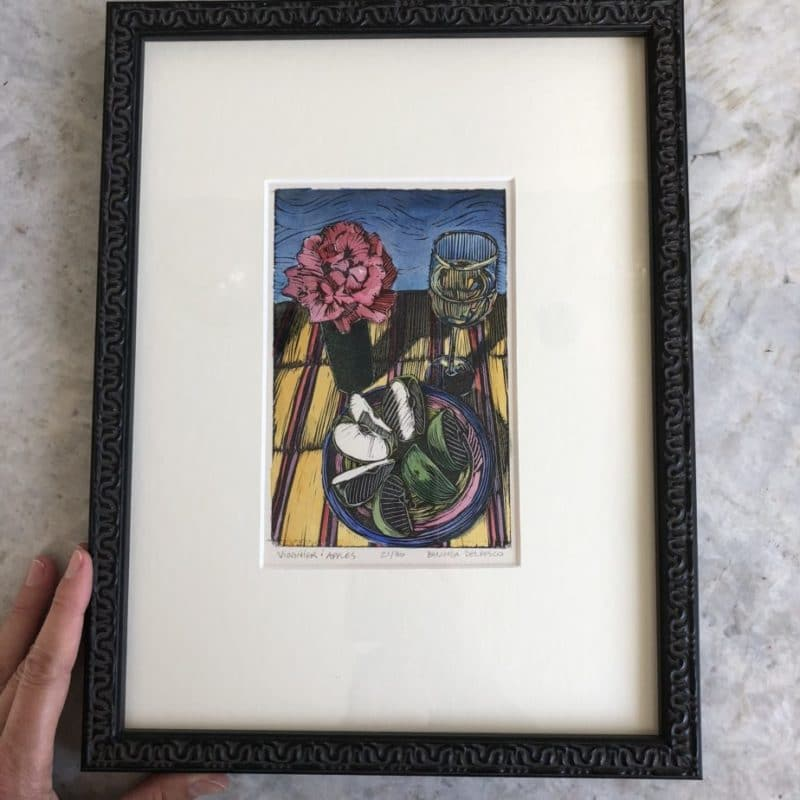 a framed linocut of sliced apples on a plate next to a bud vase with a rose in it, and a glass of white wine, on a striped table cloth