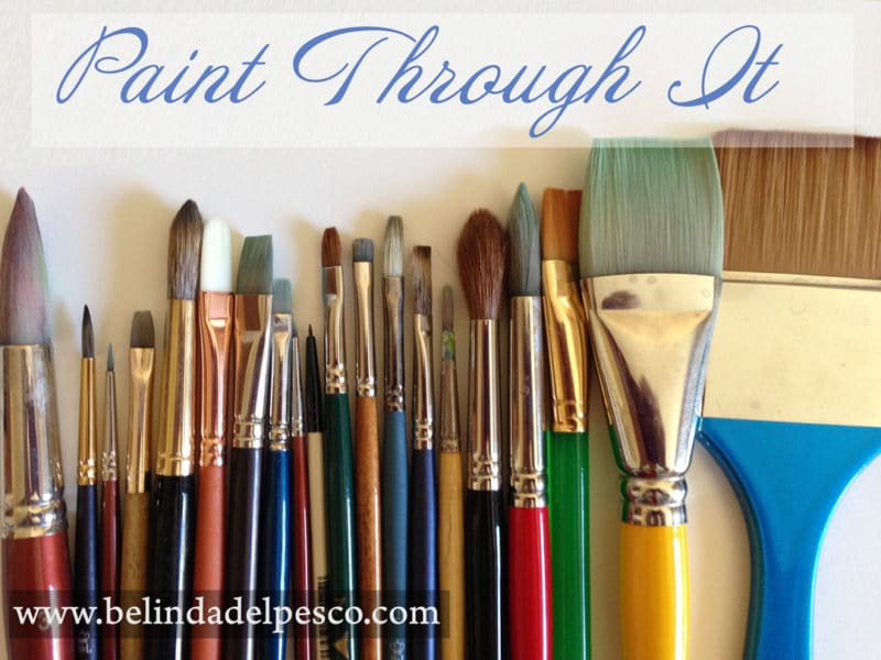 a row of artists' paint brushes lined up with encouragement to break through creative block by reaching for art supplies