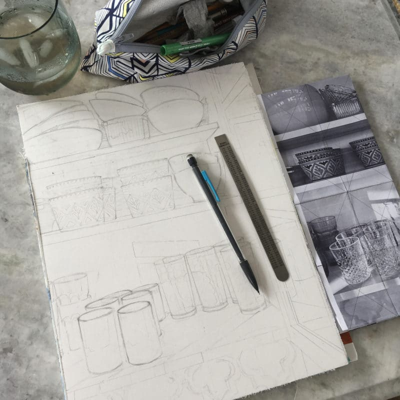 Drawing the contents of a kitchen cabinet on a watercolor block with the reference photo nearby to get ready for a watercolor painting