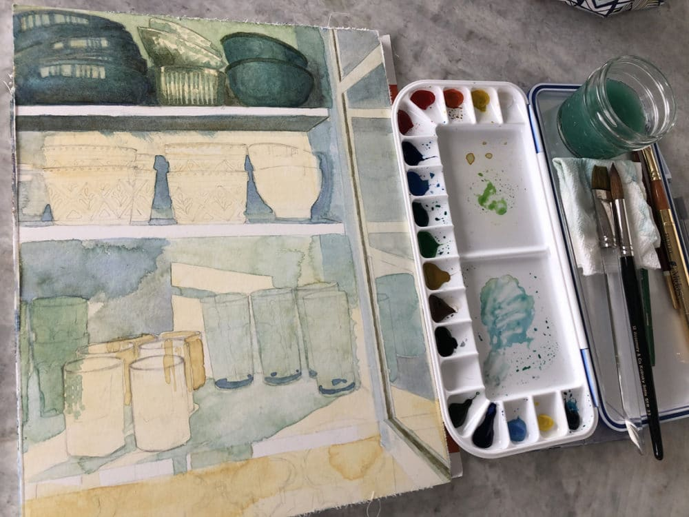 Painting a still life of the contents of a kitchen cupboard in watercolor on a painting block with a Martin sealed Palette and assorted brushes nearby