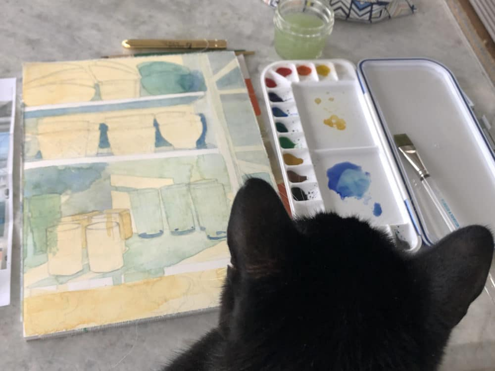 A watercolor block with the first layers of transparent color laid on a still life of the bowls and cups in a kitchen cabinet, with a paint palette nearby and a cat's head in the foreground, inspecting the progress