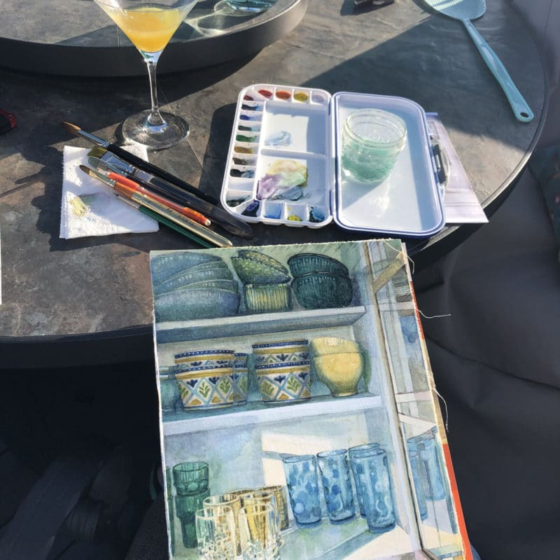 a kitchen still life of bowls and cups and glasses inside a cabinet, in process in watercolor, on a table outdoors with the paint palette and brushes nearby