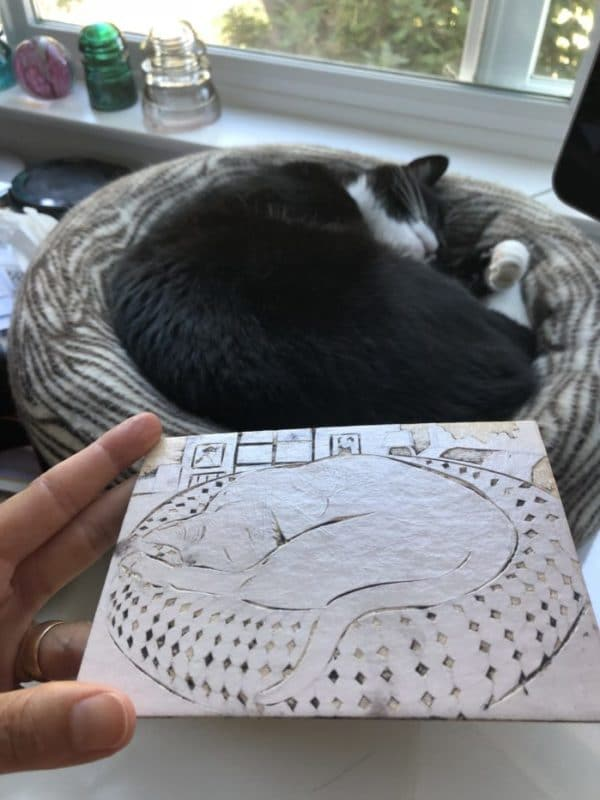 a hand holding a mat board collagraph, with some leftover ink in the grooves, near a cat sleeping curled in a donut bed, exactly like the image on the plate