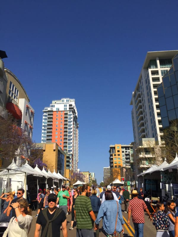 Colorful tall apartment buildings lining a street with blue skies above and a crowd of people walking the streets flanked by white artists' rents