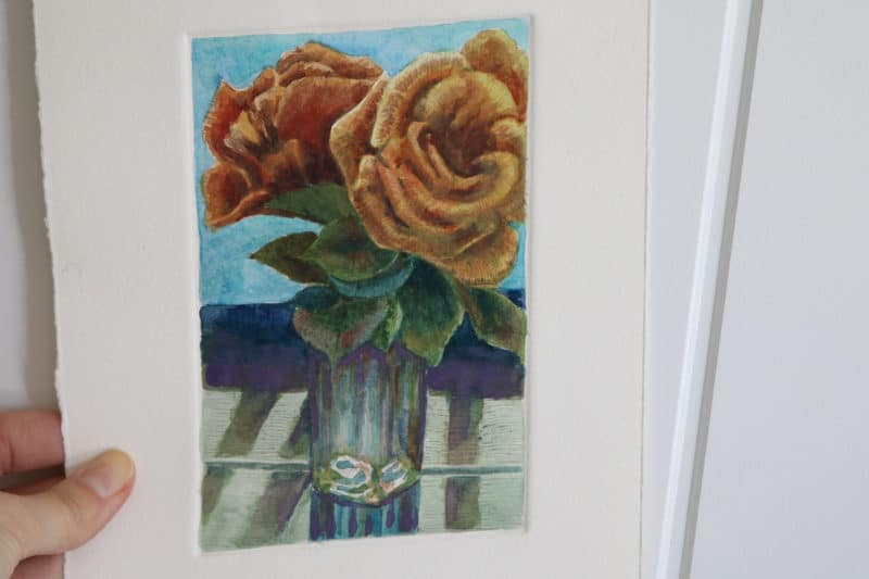 a monotype ghost print of two roses in a glass vase, painted with watercolors in shades of orange, olive green, turquoise and purple