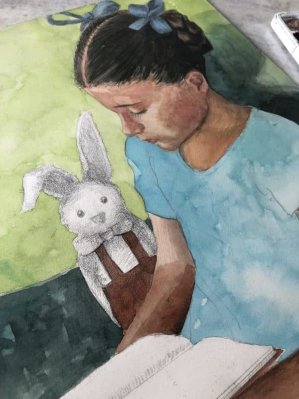 A little girl with a book painted in watercolor, and an unpainted pencil drawing of a bunny nearby.