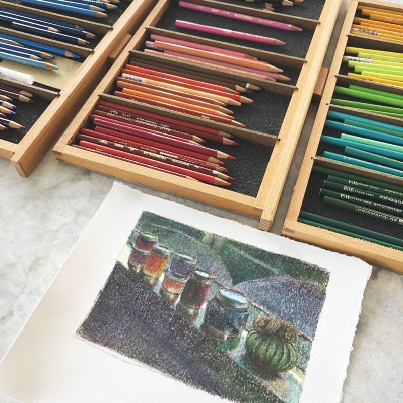 Colored pencils in tidy, color coded storage drawers, pulled out and laid around a monotype in the process of getting some added color and definition