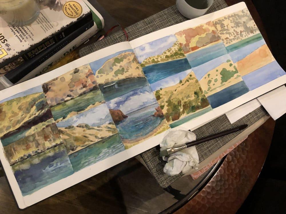a sketchbook full of watercolor landscape studies