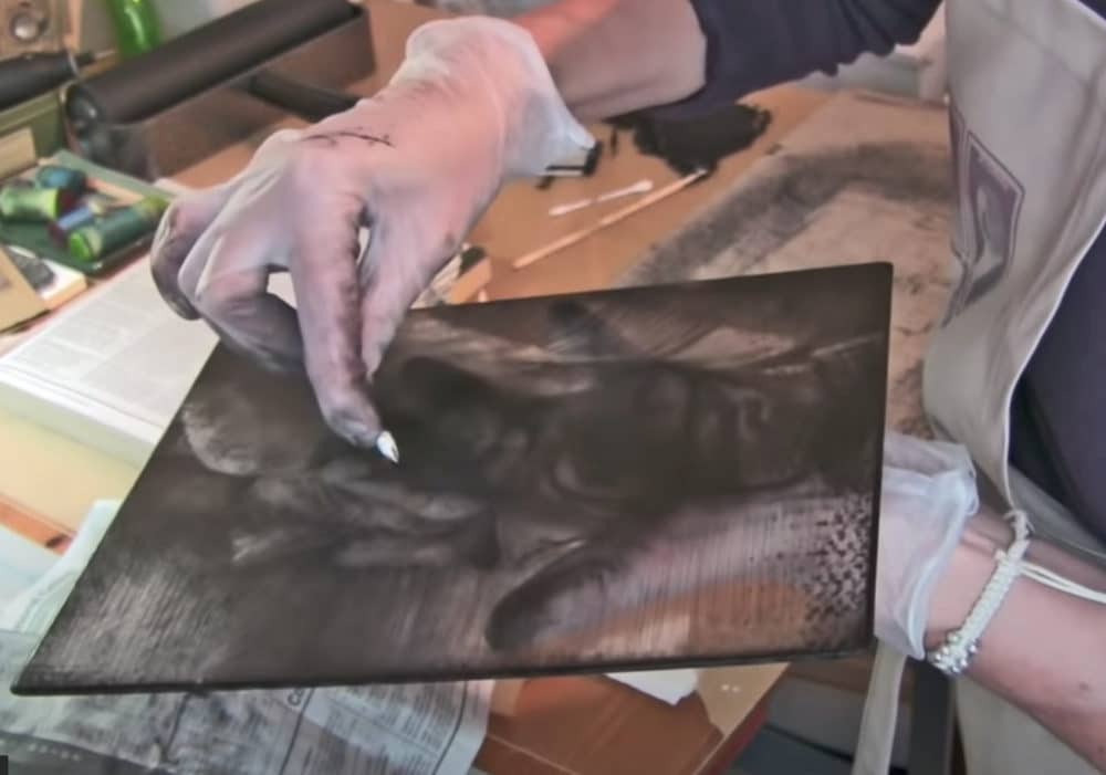 a printmaker in her studio wiping ink from a drypoint plate