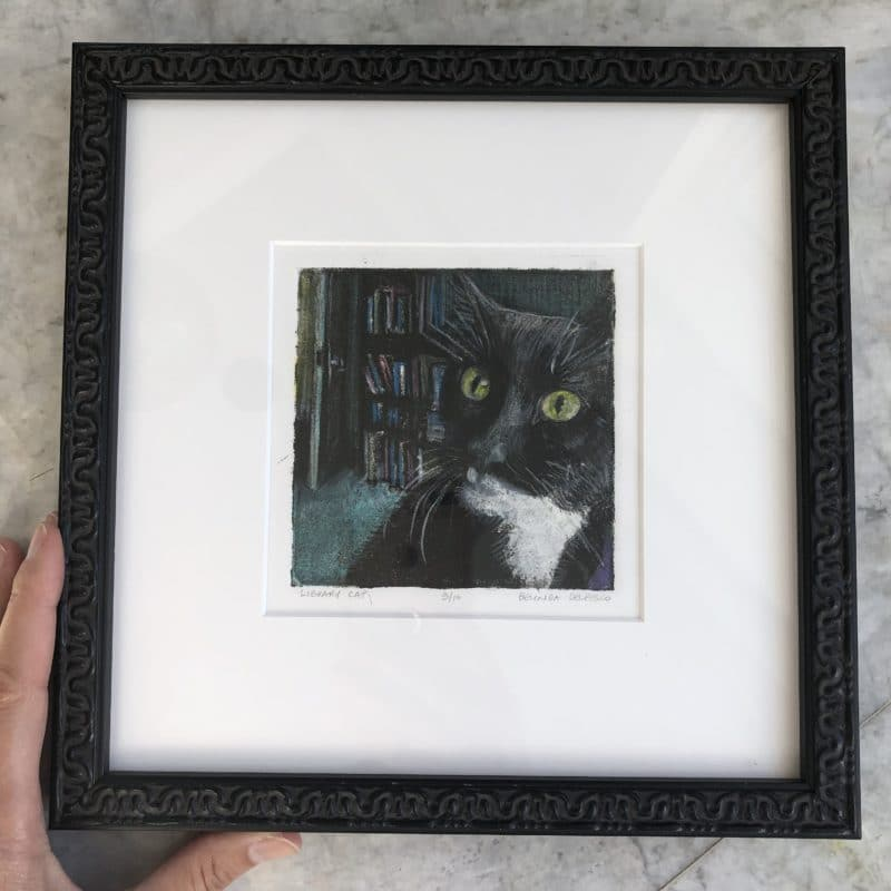 a tuxedo cat portrait in aquatint, matted and framed in black, narrow profile wood