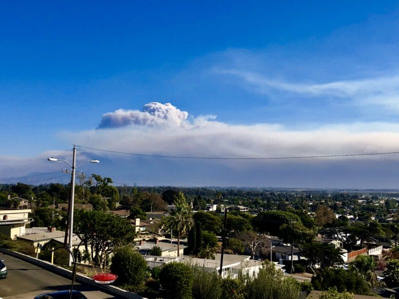 a plume of gray smoke rising in a blue sky over the city of Thousand Oaks and Malibu