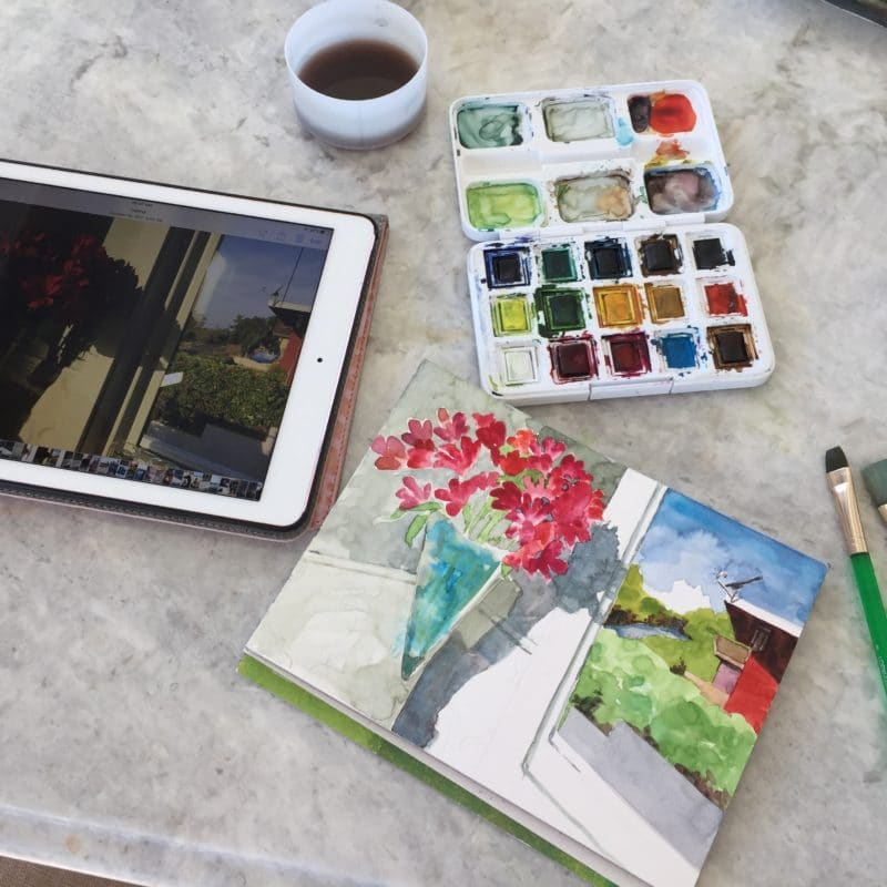 An ipad with a reference photo, a 6x8 inch watercolor sketch in early layers, a travel palette of watercolors, a rinse cup and a paint brush
