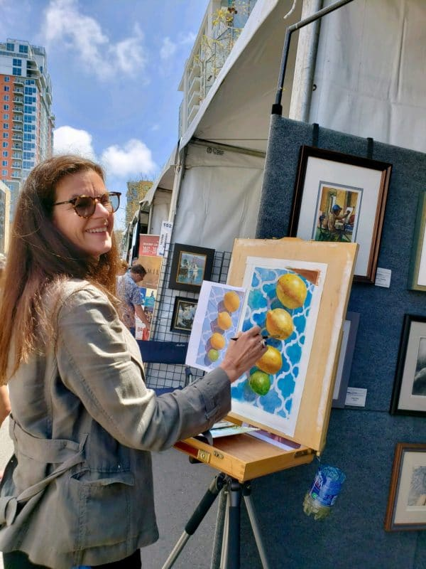 an artist standing at an easel on a sunny day in front of a row of art booths painting a watercolor