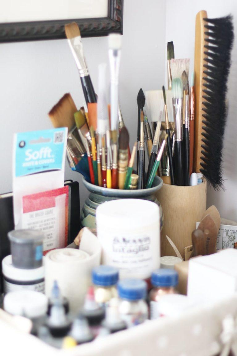 art studio brushes and ink stored in pretty ceramic containers