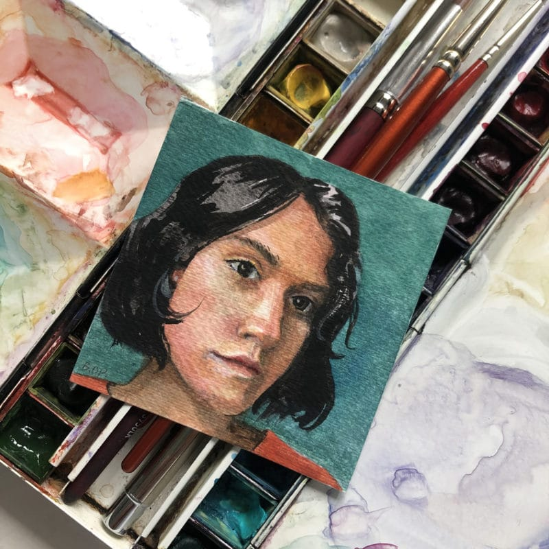 a tiny watercolor painting of a woman with bobbed black hair and a thoughtful look on her face