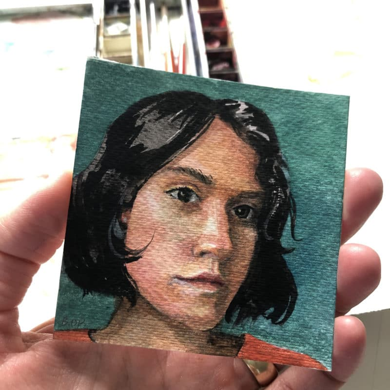 a small watercolor painting of a young woman with short dark hair