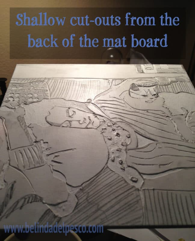 a mat board collagraph plate, in process, showing carved and peeled shapes that represent a figure laying down, with a cat sleeping on her torso.