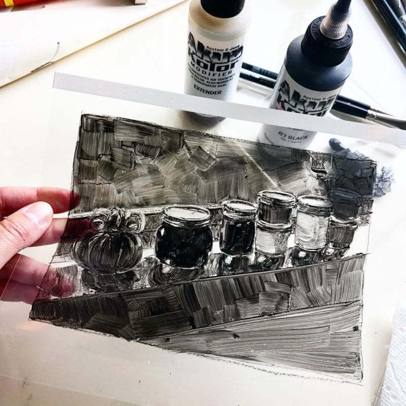 a hand holding a clear sheet of plastic with a black ink still life rendered in printmaking ink