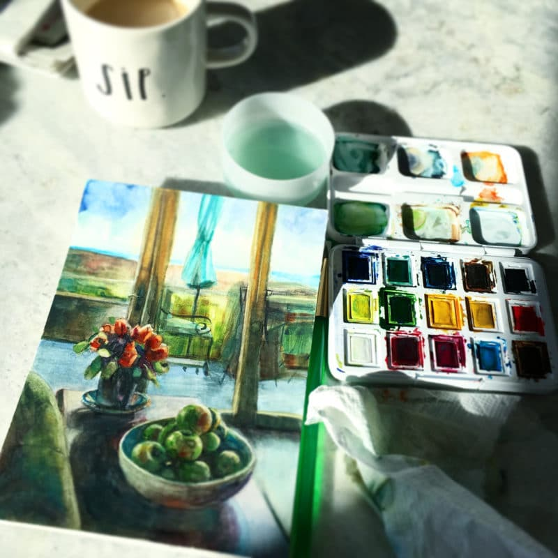 a watercolor in process, a van gogh pocket box palette and a cup of coffee