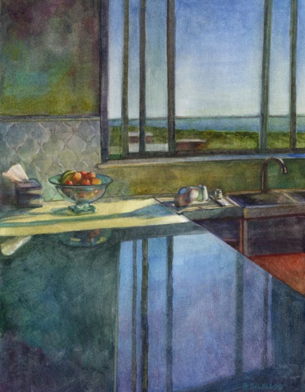 a kitchen counter with a window in the background throwing reflections of the sky across the countertop