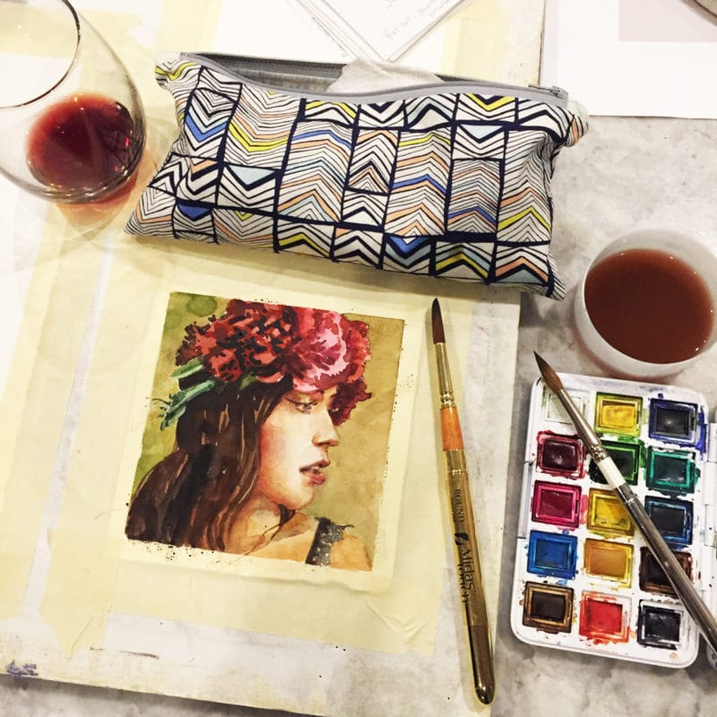 painting small watercolor portraits on the kitchen counter, with a glass of wine