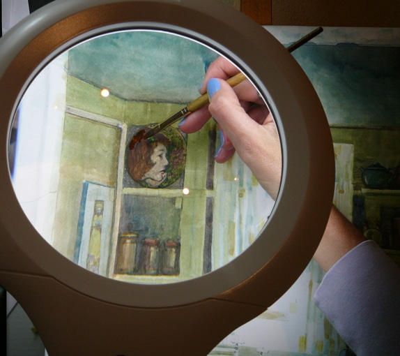 using a magnifier light to paint tiny details of a face in profile