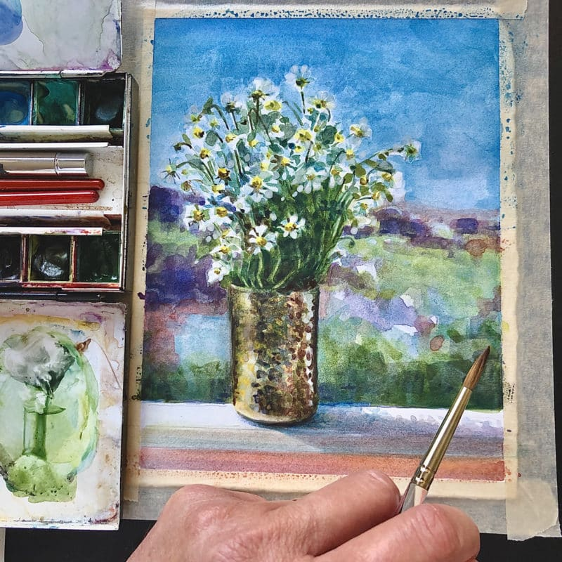 a watercolor of white flowers next to a painting palette and the hand of the artist at work in the studio