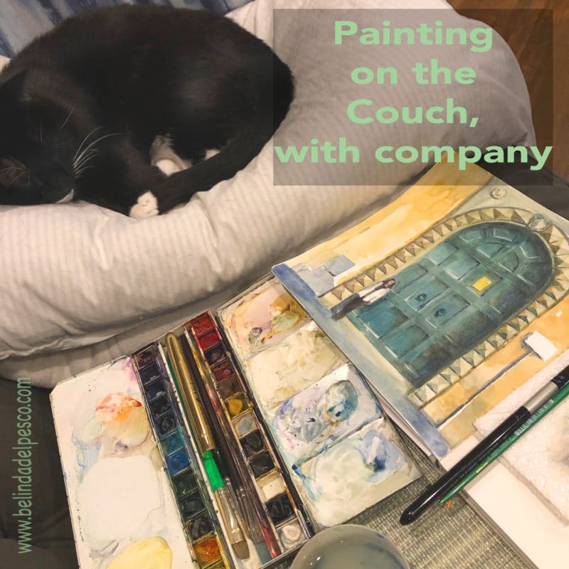 a black cat is curled on a pillow sleeping next to a lap desk on a couch with a watercolor painting of a door in process, and a watercolor palette and brushes