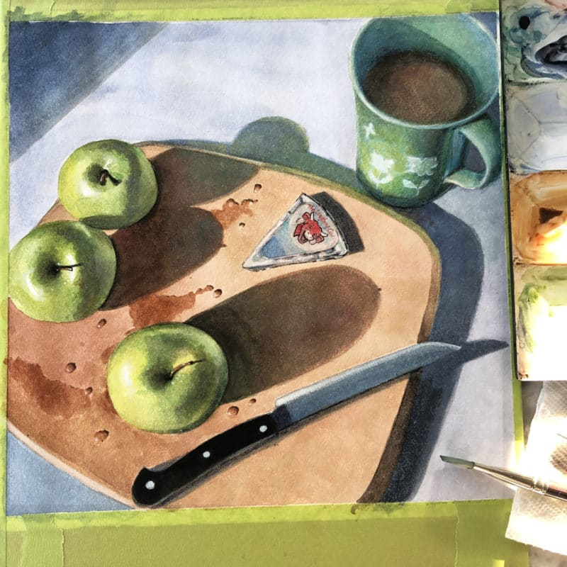 a watercolor painting still life in progress with apples, a knife and a wedge of laughing cow cheese