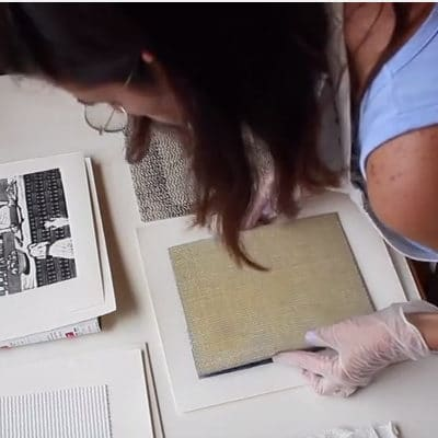 a woman in an art studio, leaning over her work table to align a linocut block over paper to make a print