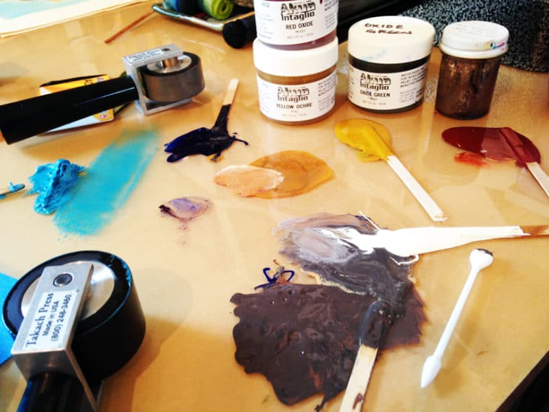 printmaking supplies and ink on a glass topped table