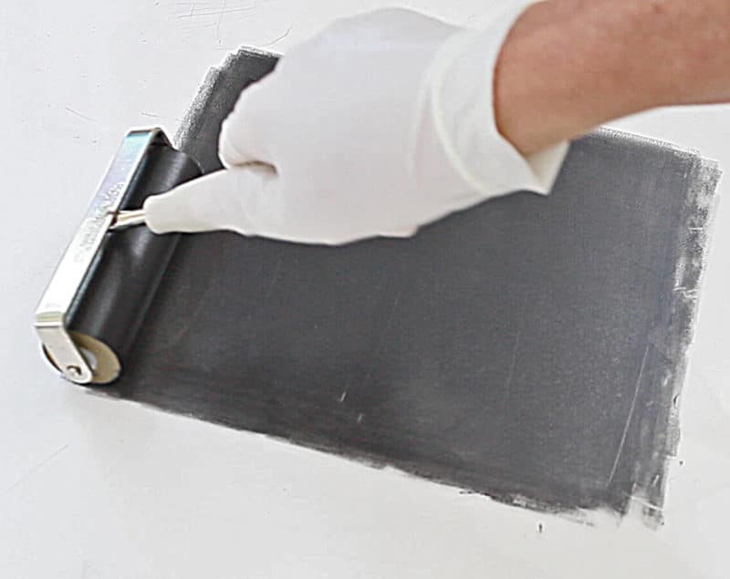 To make a transfer drawing monotype print, first, you roll black ink evenly onto a smooth surface with a rubber brayer