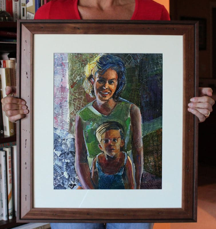 A torn tissue paper collage portrait of a mother and child, framed and held up by the artist to give the artwork a sense of scale