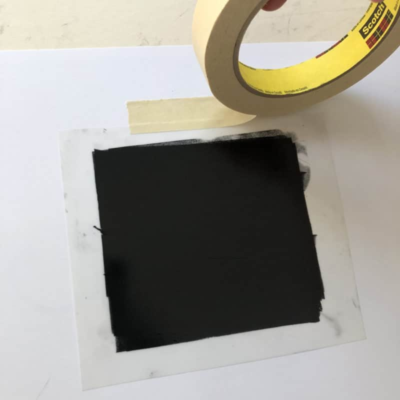 taping a sheet of mylar to a table after its coated with black printmaking ink
