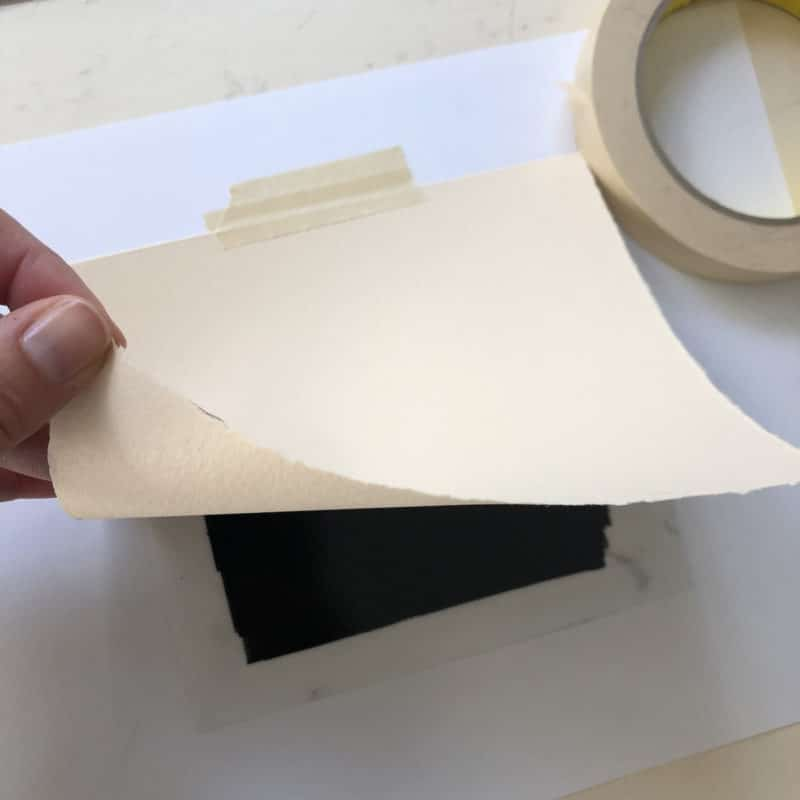 Taping a small sheet of dry BFK Rives printmaking paper over inked drafting film to make a trace monotype
