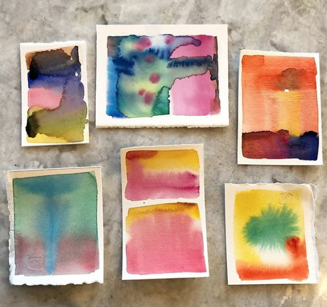 Six tiny scaps of watercolor paper with color watercolor washes in random colors